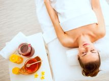 Woman laying on massage table near honey spa therapy ingre. Young woman laying on massage table near honey spa therapy ingredients royalty free stock photo
