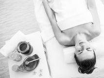 Woman laying on massage table near honey spa therapy ingre. Young woman laying on massage table near honey spa therapy ingredients stock photography
