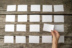 Woman laying out blank white memo notes Stock Images