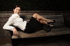 Woman laying on a park bench Stock Images