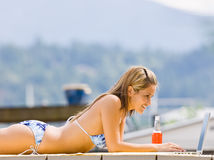 Woman laying on pier on laptop Royalty Free Stock Images