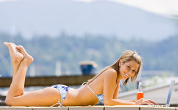 Woman laying on pier on laptop Stock Photos