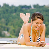 Woman laying on pier listening to music player Stock Image