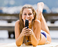 Woman laying on pier text messaging Royalty Free Stock Photography