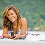 Woman laying on pier text messaging Stock Photo