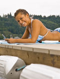 Woman laying on pier text messaging Royalty Free Stock Photo