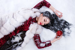Woman laying on a snow near the bitten apple Stock Photo