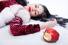 Woman laying on a snow near the bitten apple Stock Photos