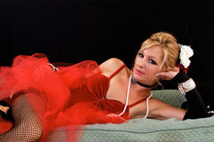 Woman laying on sofa. Beautiful blonde laying on chaise lounge.dressed up as old fashioned madam or prostitute can also be a sexy mrs. claus or santa's elf for Stock Images
