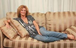 Woman laying on sofa Stock Image