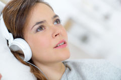 Woman laying on sofa with headphones on stock photo