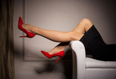 Woman laying in sofa with red high heels on Stock Photography