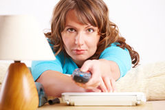 Woman laying on sofa with remote controller Royalty Free Stock Image