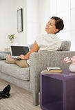 Woman laying on sofa and using laptop. Rear view Royalty Free Stock Images