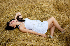 Woman is laying on a straw Stock Image