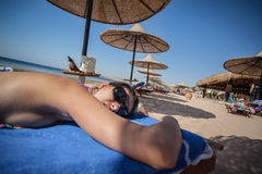Woman laying on sunbed. Under umbrella. Seashore, sand beach. Laying on stomach Royalty Free Stock Photo