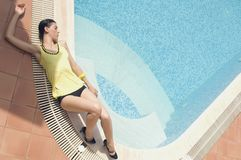 Woman laying on the swimming pool edge Stock Photos