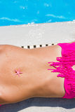 Woman laying by the swimming pool with a starfish on her belly Stock Photography