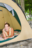 Woman laying in tent using cell phone Stock Image