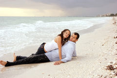 Woman laying on top of man at beach looking at vie. A beautiful you lady is laying on top of a man at the beach, their clothes are wet and she is looking at Stock Image