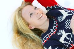 Woman Laying in Winter Snow. A 30 year old, attractive, smiling woman wearing a Christmas ski sweater, is lying in the winter snow outside Royalty Free Stock Image