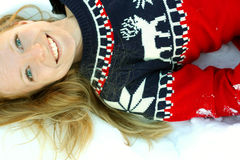 Woman Laying in Winter Snow. A 30 year old, smiling woman wearing a Christmas ski sweater, is lying in the winter snow outside Royalty Free Stock Photography