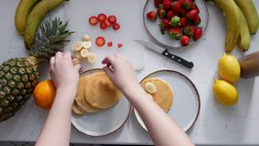 A woman lays bananas on pancakes and pours condensed milk stock footage