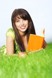 Woman lays on grass and reads book. Stock Images