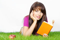 Woman lays on green field. Beautiful woman lays on green field and reads book Royalty Free Stock Image