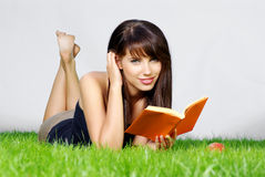 Woman lays on green field and reads book. Young beautiful woman lays on green field and holding apple Stock Photos