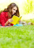 Woman lays on green field and reads book. Royalty Free Stock Image