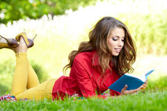 Woman lays on green field and reads book. Royalty Free Stock Images