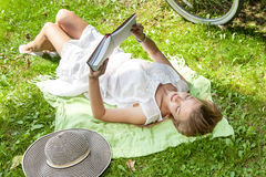 Woman lays on green grass reading book in city park Royalty Free Stock Images