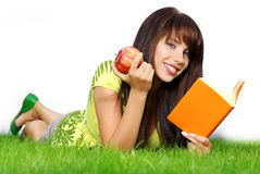 Woman lays on green grass and reads book. royalty free stock images
