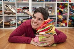 Happy craft person at home. Woman lays on her pile of colorful fat quarters in her craft space royalty free stock photo