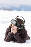 Woman lays in the snow, with vr glasses Royalty Free Stock Photography