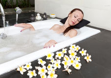 The young slender long-haired woman accepts a bathtub on the dug-out air Stock Photography