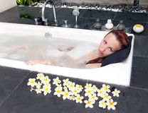 The woman accepts a bathtub on the dug-out air with petals of flowers Royalty Free Stock Image