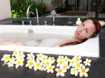 The young slender long-haired woman accepts a bathtub with petals of flowers Royalty Free Stock Images