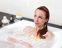 Woman lays in soapsuds in bathing, full water.Close up in a sunny day Royalty Free Stock Images