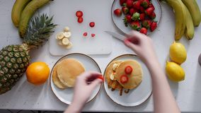 A woman lays stawberry on pancakes and pours condensed milk stock video footage