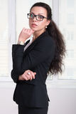 Woman leader in black business suit and glasses standing turned Royalty Free Stock Photos