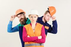 Woman, leader in hard hat with serious face stand. In front of builders. Lady boss concept. Team of architects, builders, labourers peeking behind woman stock photography