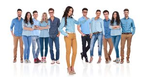 Woman leader presenting her young casual group behind her. While standing relaxed on white background with a hand in pocket royalty free stock image