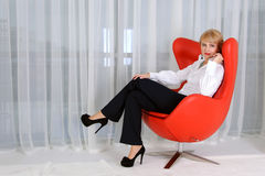 Woman, leader, who sits in a red chair Royalty Free Stock Photography