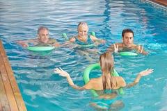 Woman leading aqua fitness class. Young women leading aqua fitness class for senior people in swimming pool Royalty Free Stock Photo