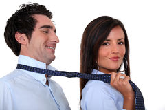 Woman leading a man. Woman leading a men by his tie Stock Image