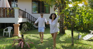 Woman Leading Man Walking In Tropical Garden Near Villa House, Happy Couple Outdoors Lovers On Vacation stock video footage