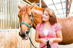 Woman leading pony - horse stable Stock Image