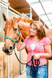 Woman leading pony - horse stable Stock Photography